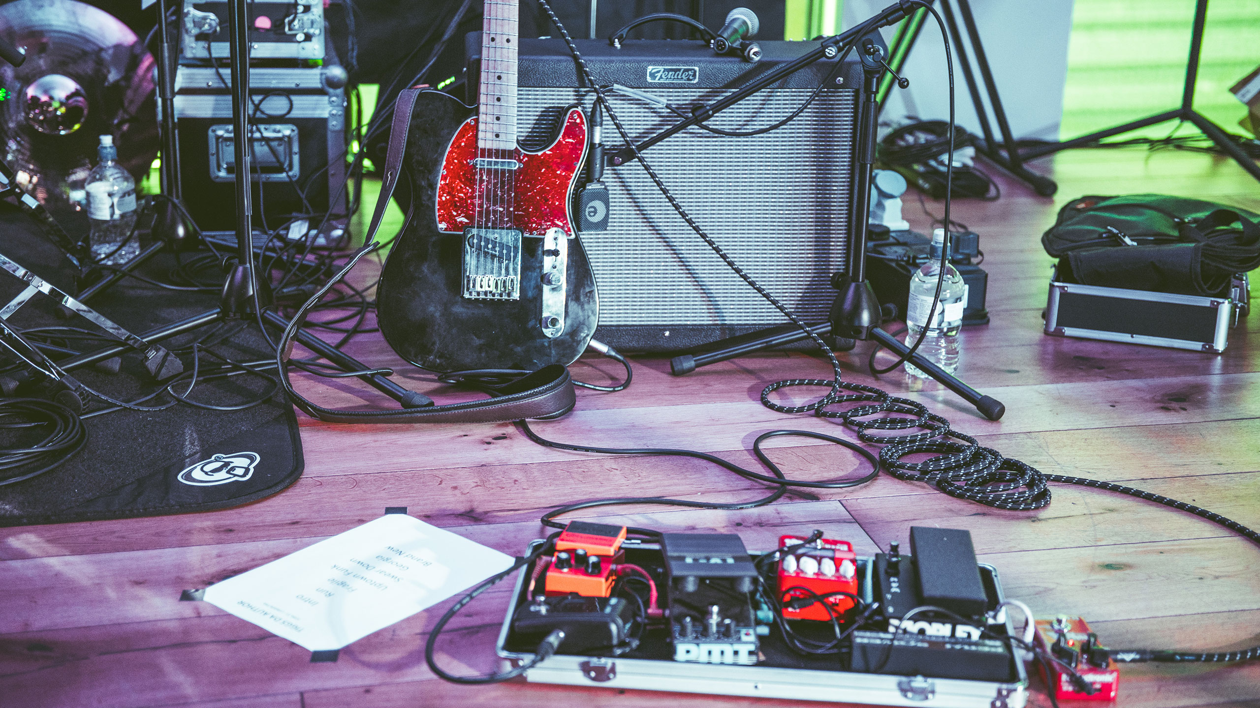 A guitar, amp and pedals on a stage ready for a gig