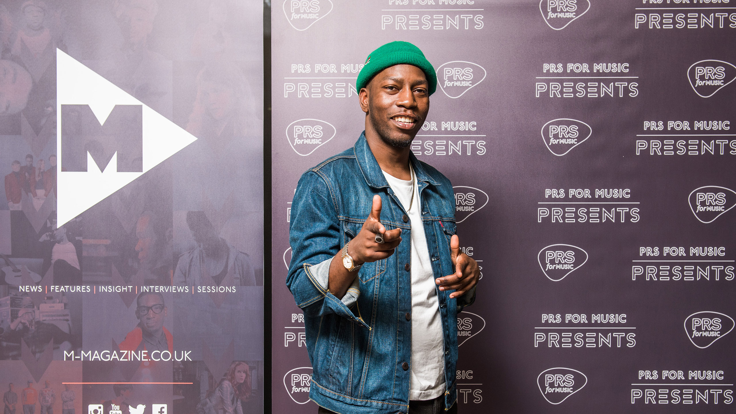 Tiggs Da Author points at the camera in front of the PRS for Music backdrop, wearing a green beanie hat, white t shirt and denim jacket