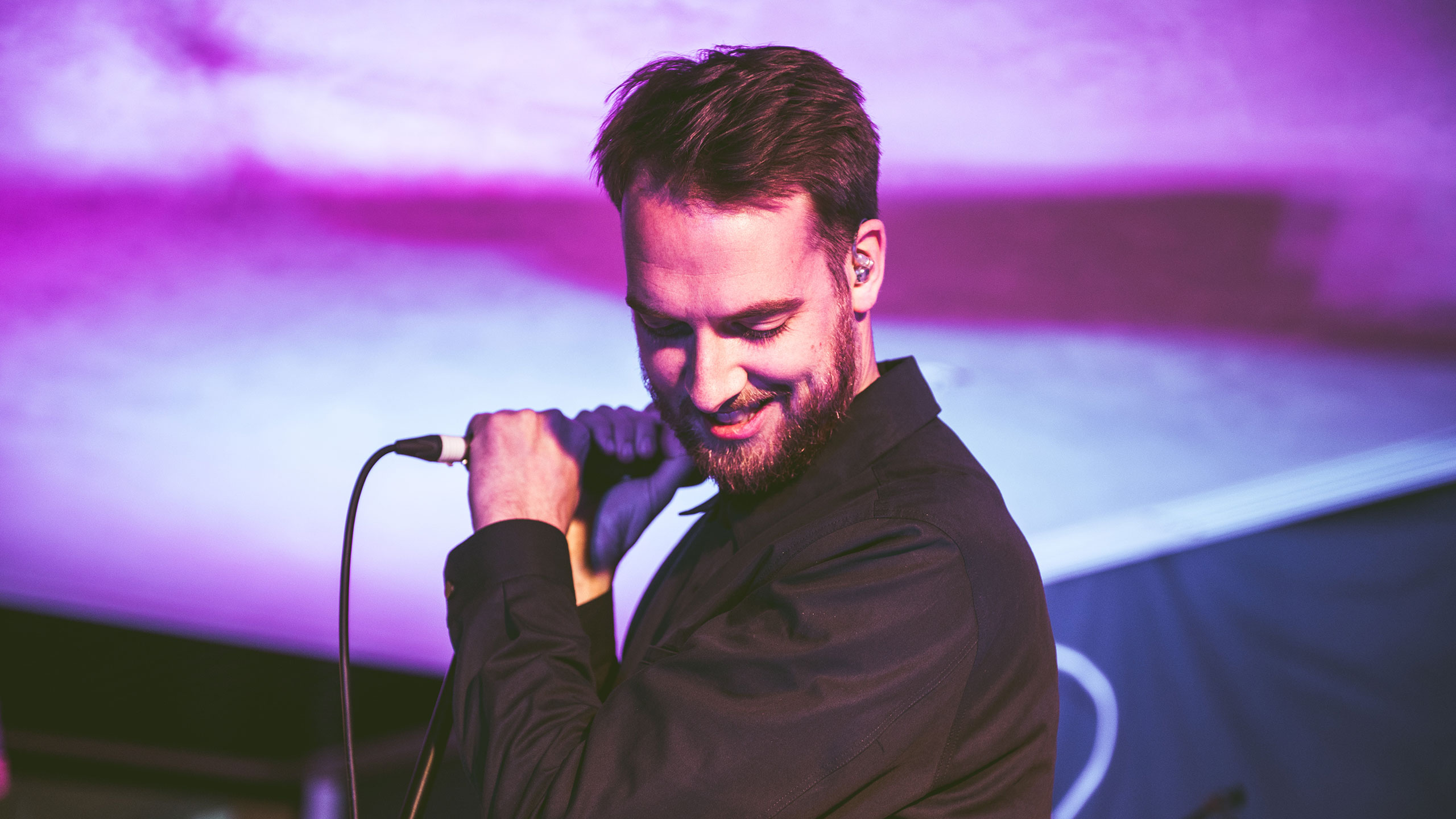 Honne's Andy Clutterbuck looks down and smiles on stage at PRS Presents