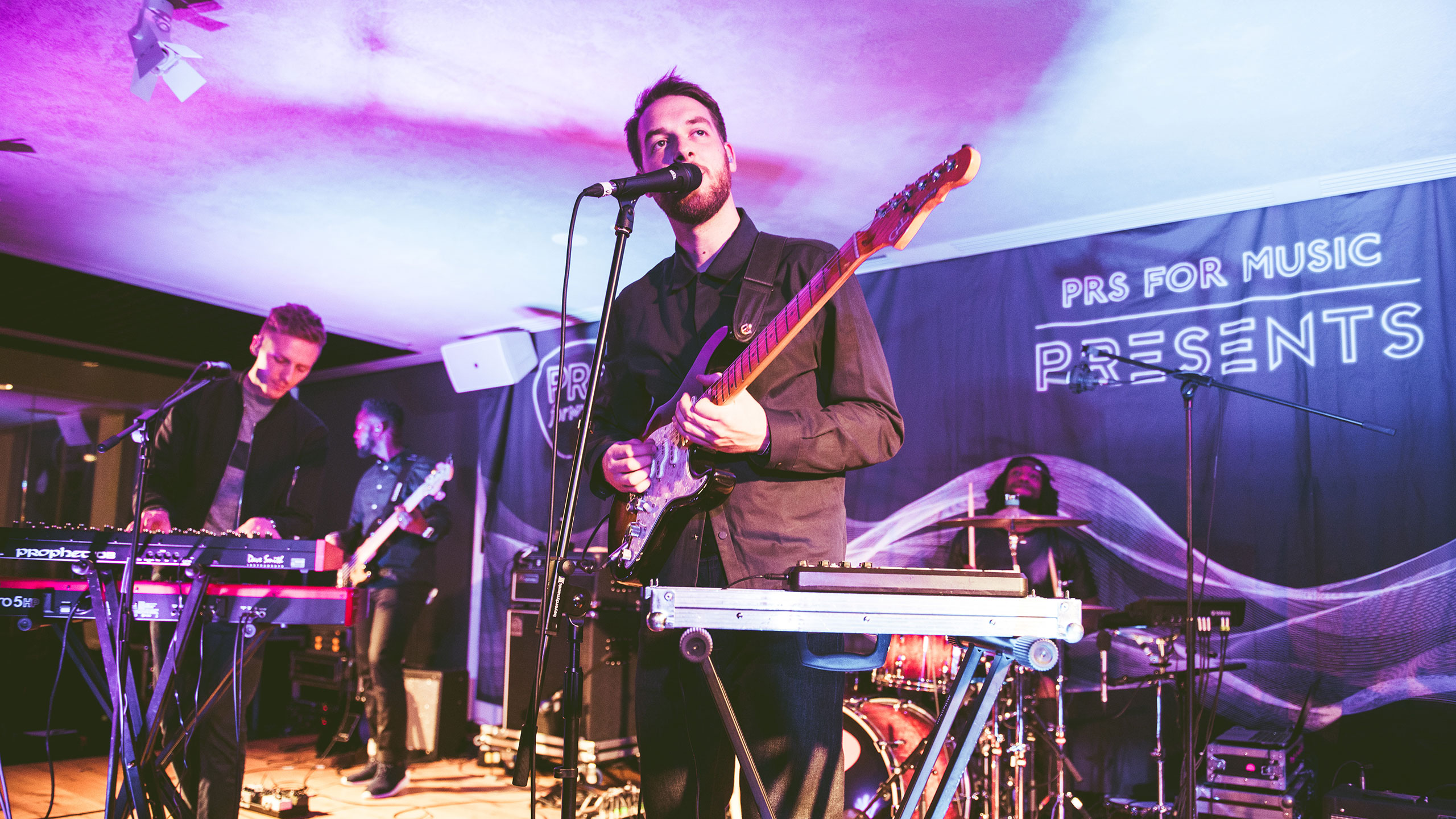 Honne perform guitar, vocals and synth with a bass player and drummer, on stage at PRS Presents
