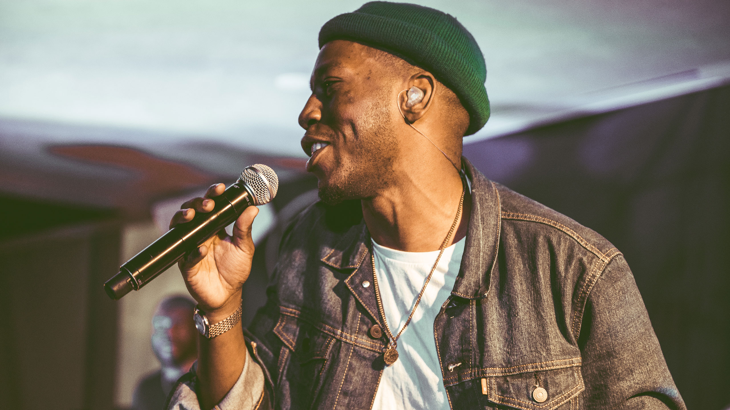 Tiggs Da Author singing into a microphone, wearing a green hat and denim jacket, at PRS Presents