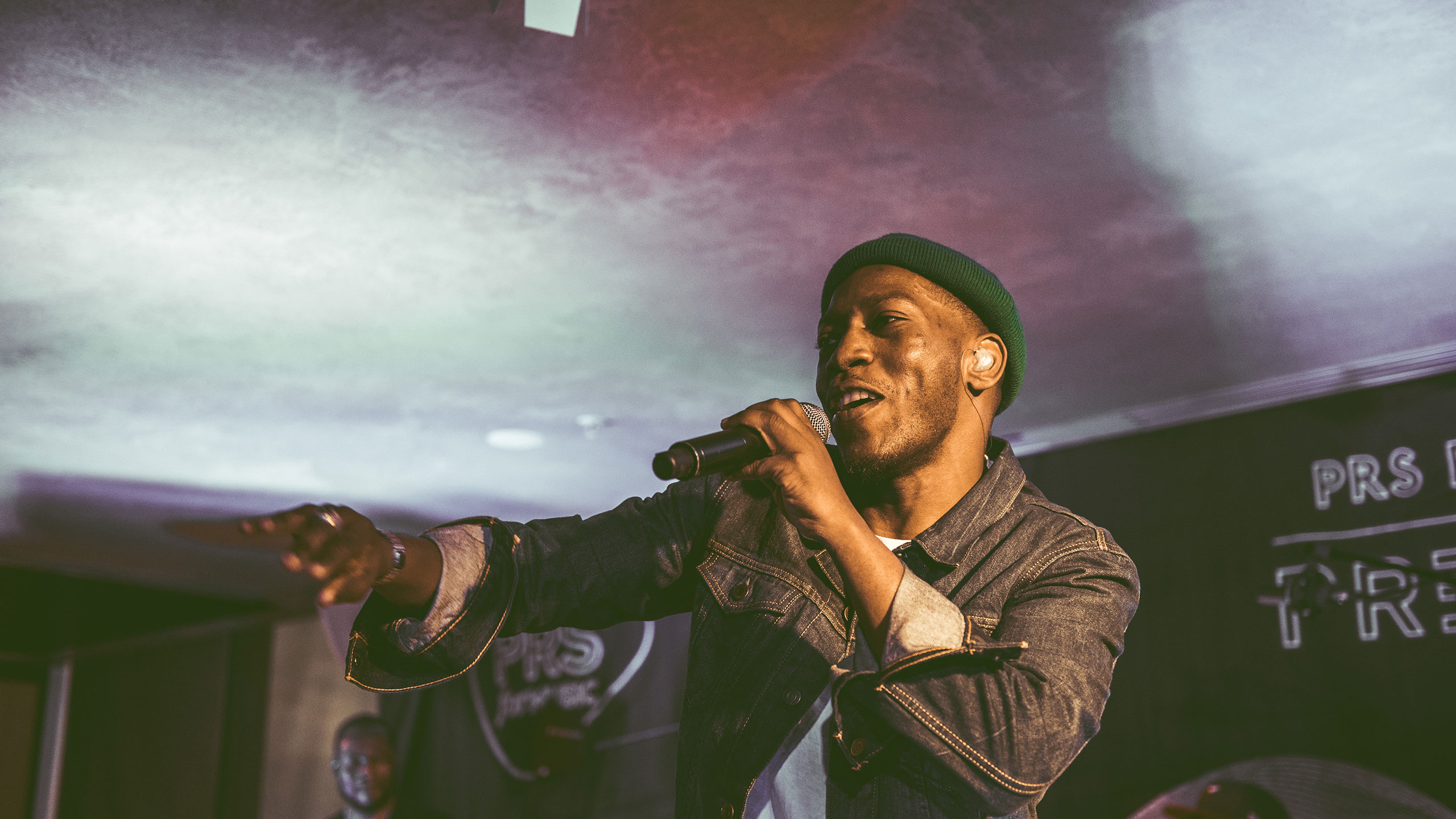 Tiggs Da Author points into the crowd as he performs at PRS Presents, wearing a green hat and denim jacket