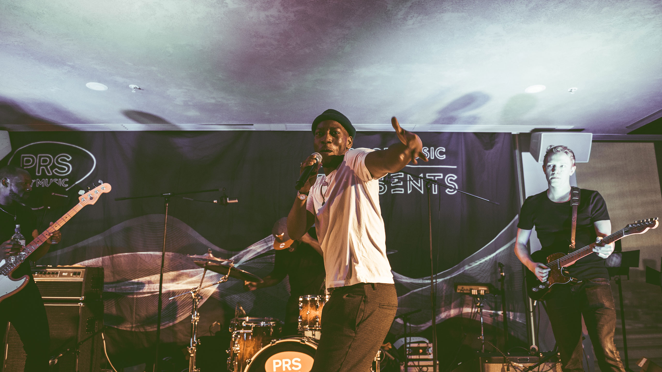 Tiggs Da Author points at the crowd during his performance at PRS Present, wearing a white t shirt, as his live band plays behind him