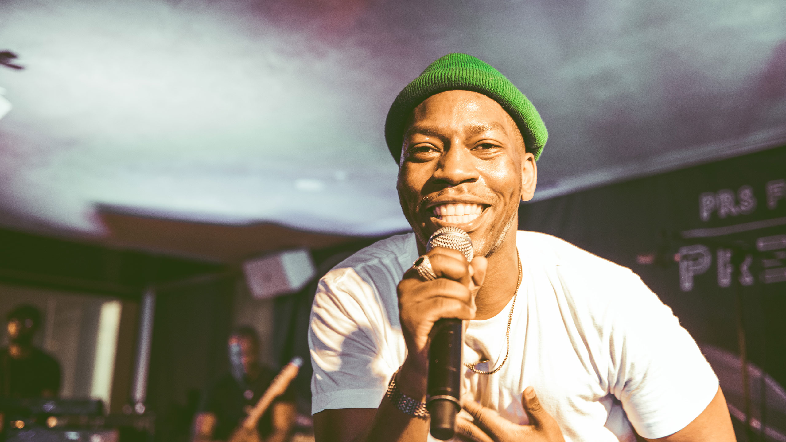 Tiggs Da Author smiles into the camera with his microphone at PRS Presents, wearing a green hat and white t shirt