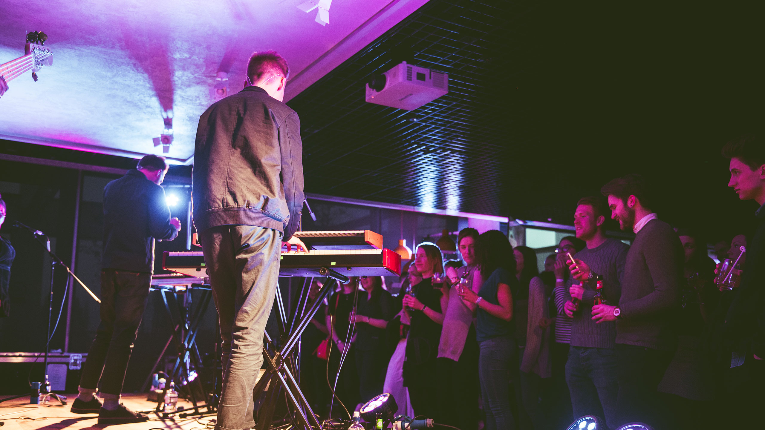 A shot from behind Honne performing keyboards and singing on stage at PRS Presents, the audience are chatting