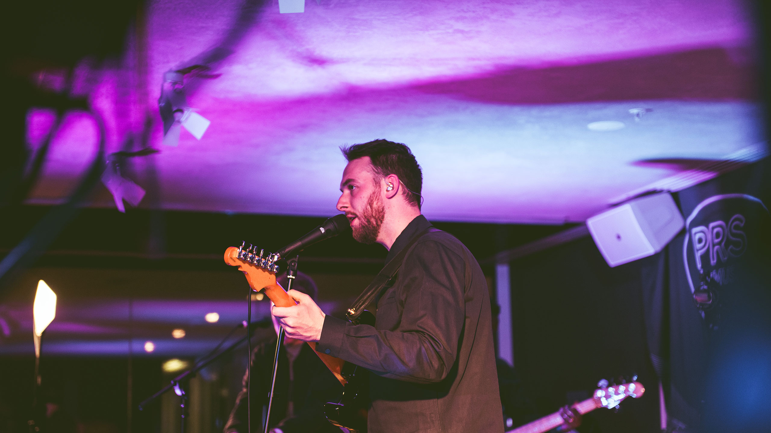 A shot from the side of Honne's Andy Clutterbuck singing and playing guitar on stage at PRS Presents