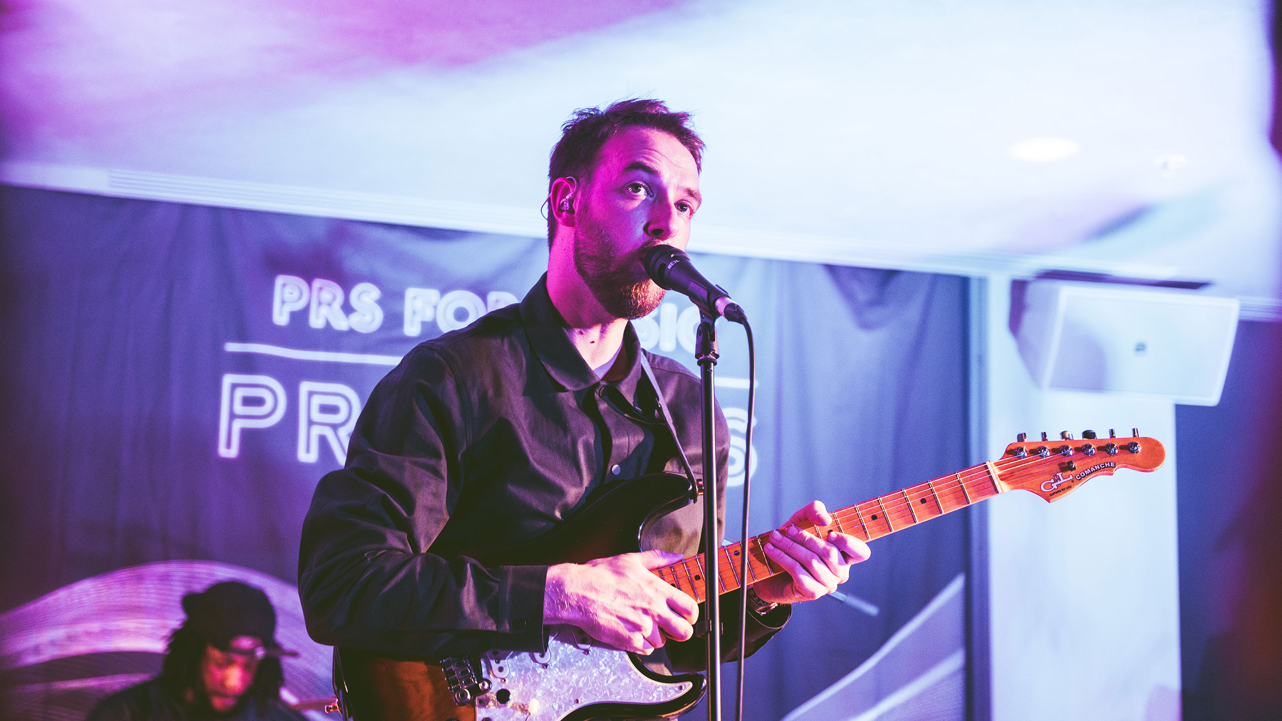 Honne's Andy Clutterbuck plays guitar and sings at PRS Presents, wearing a dark shirt