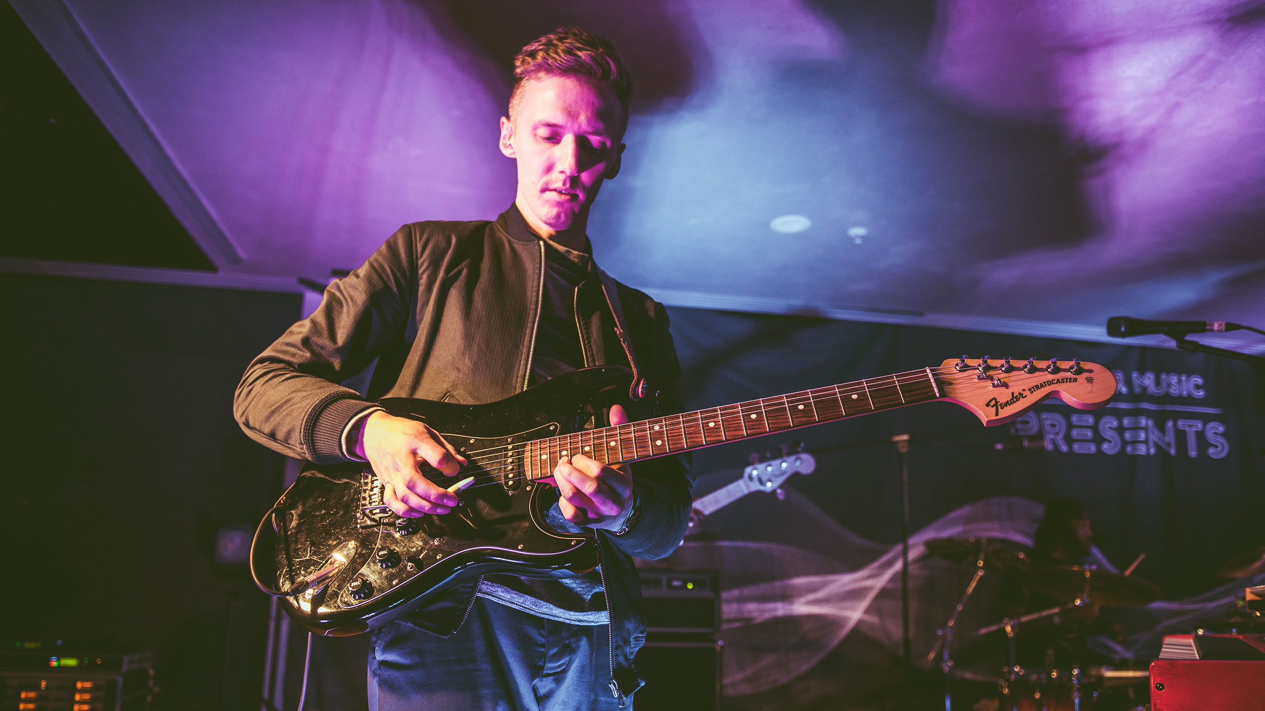 Honne's James Hatcher plays a black guitar on stage at PRS Presents, wearing a dark shirt