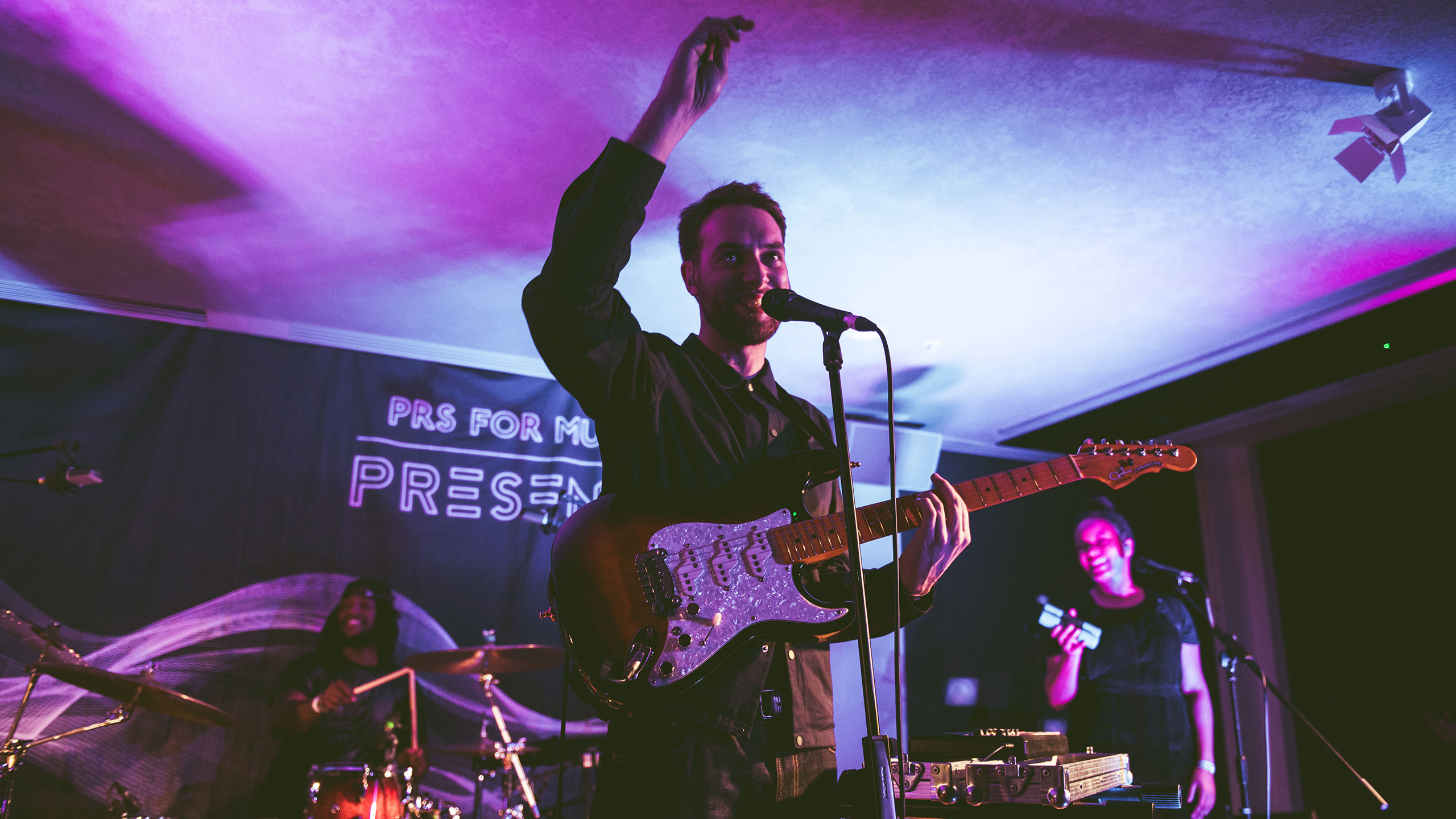 Honne's Andy Clutterbuck raises his arm as he sings and plays guitar at PRS Presents
