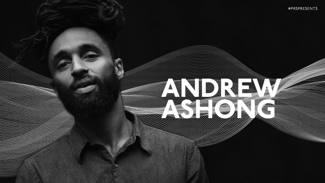 A black and white image of Andrew Ashong, wearing a dark shirt, looking at the camera, with a graphic background for PRS for Music Presents