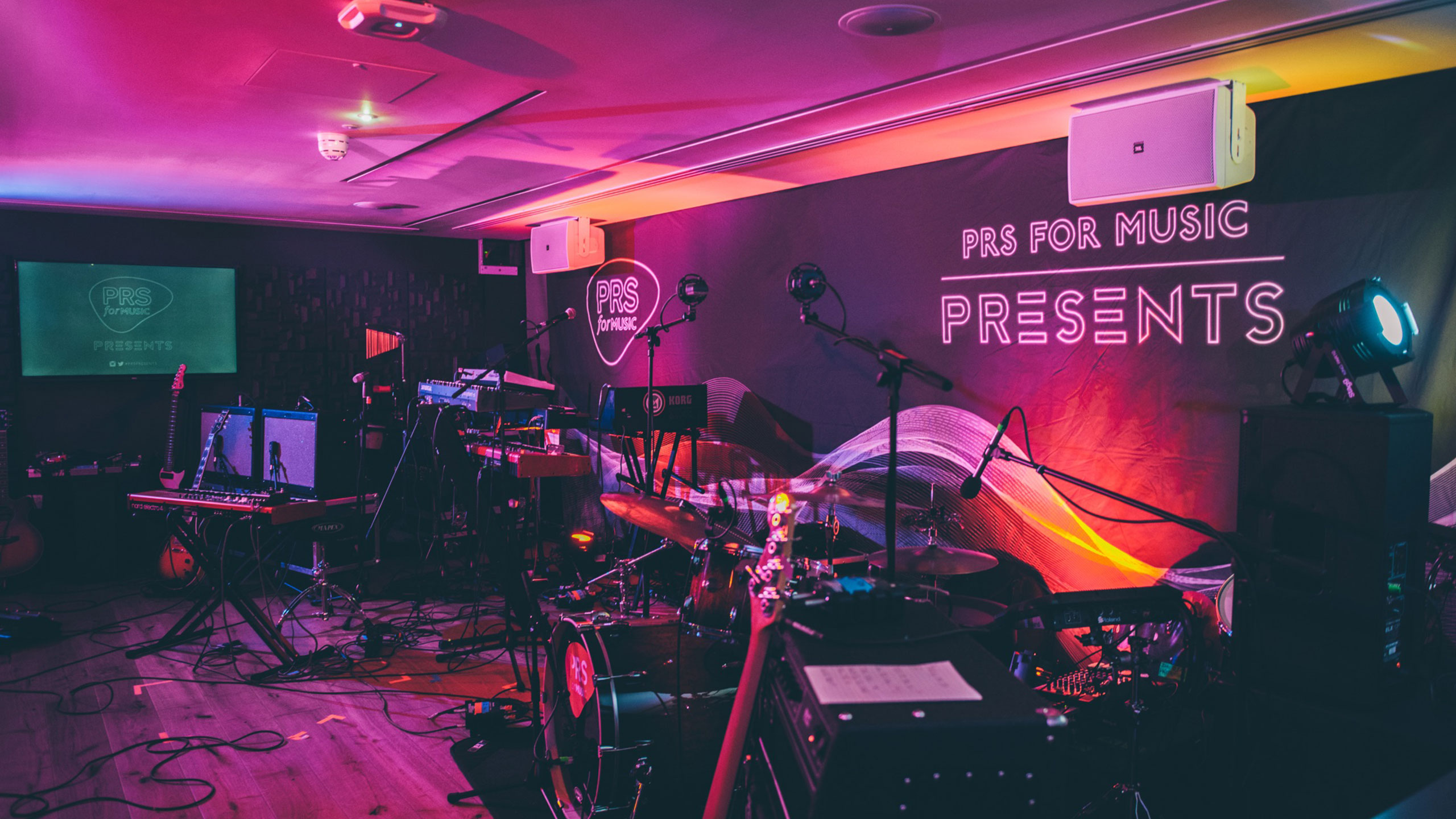 A stage set up ready for a live gig, with PRS for Music Presents as the backdrop