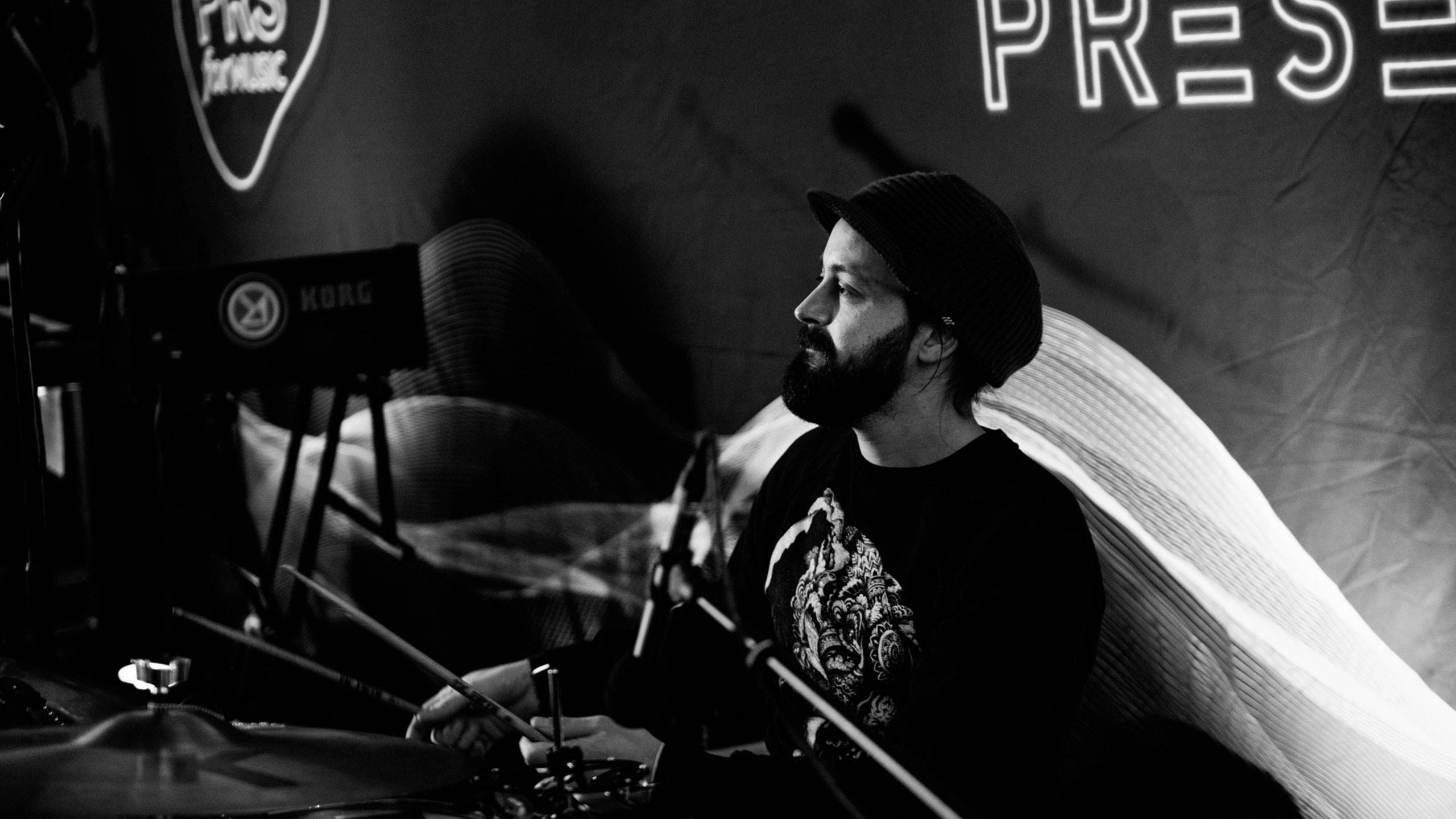 A black and white photo of a drummer, wearing a peaked hat, live at PRS for Music Presents