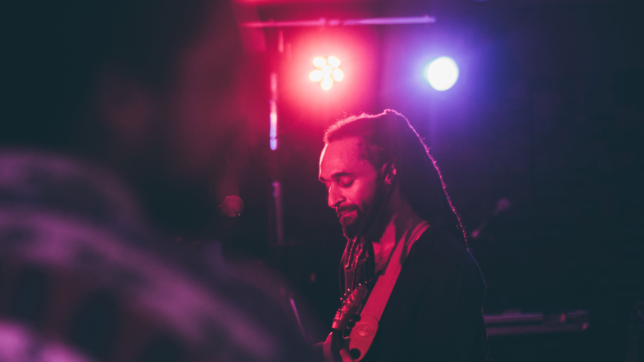 Andrew Ashong, with long dreadlocks and a dark shirt, looks down at his guitar on stage at PRS for Music Presents