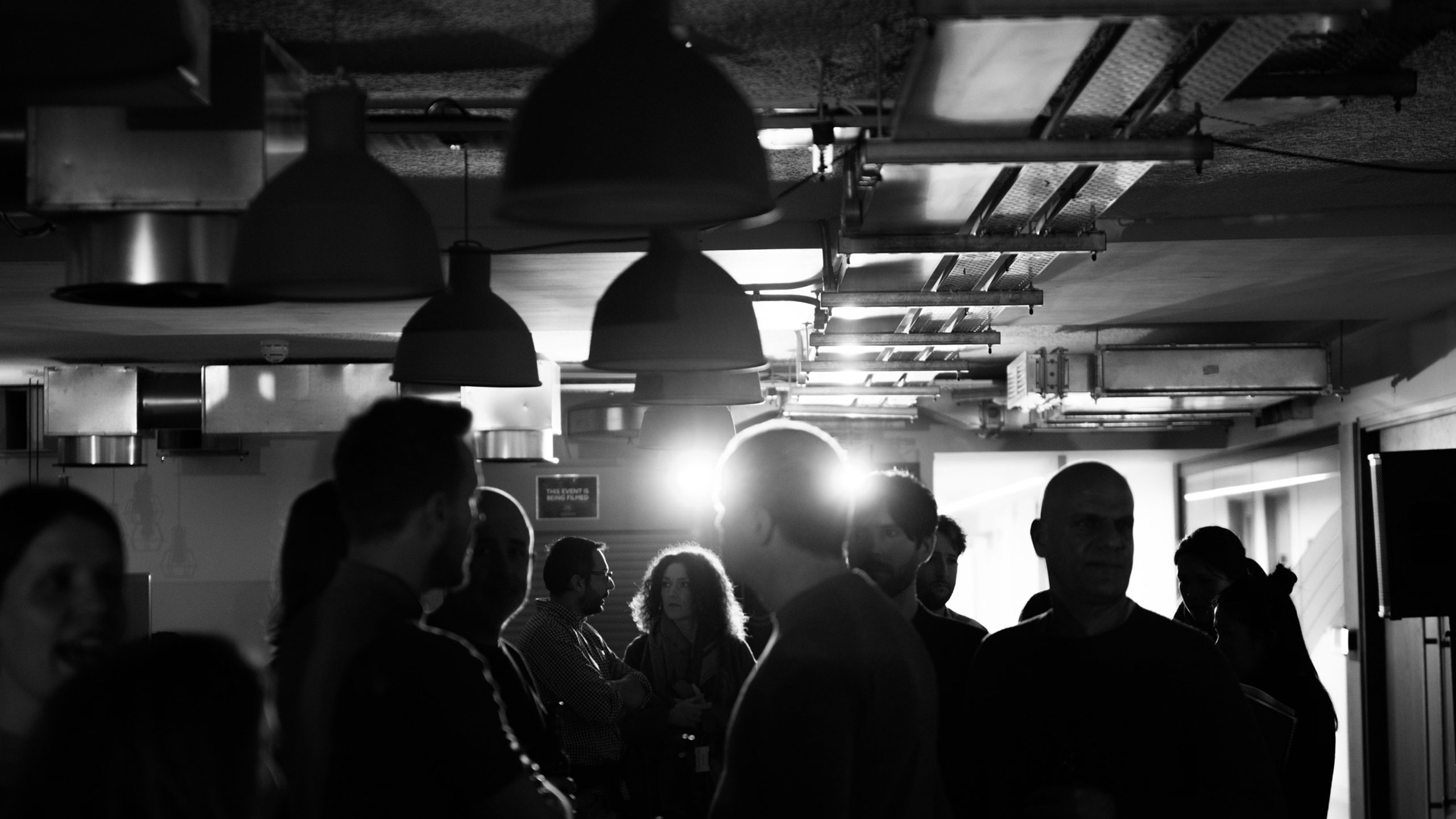 A black and white photo of audience members chatting at PRS for Music Presents