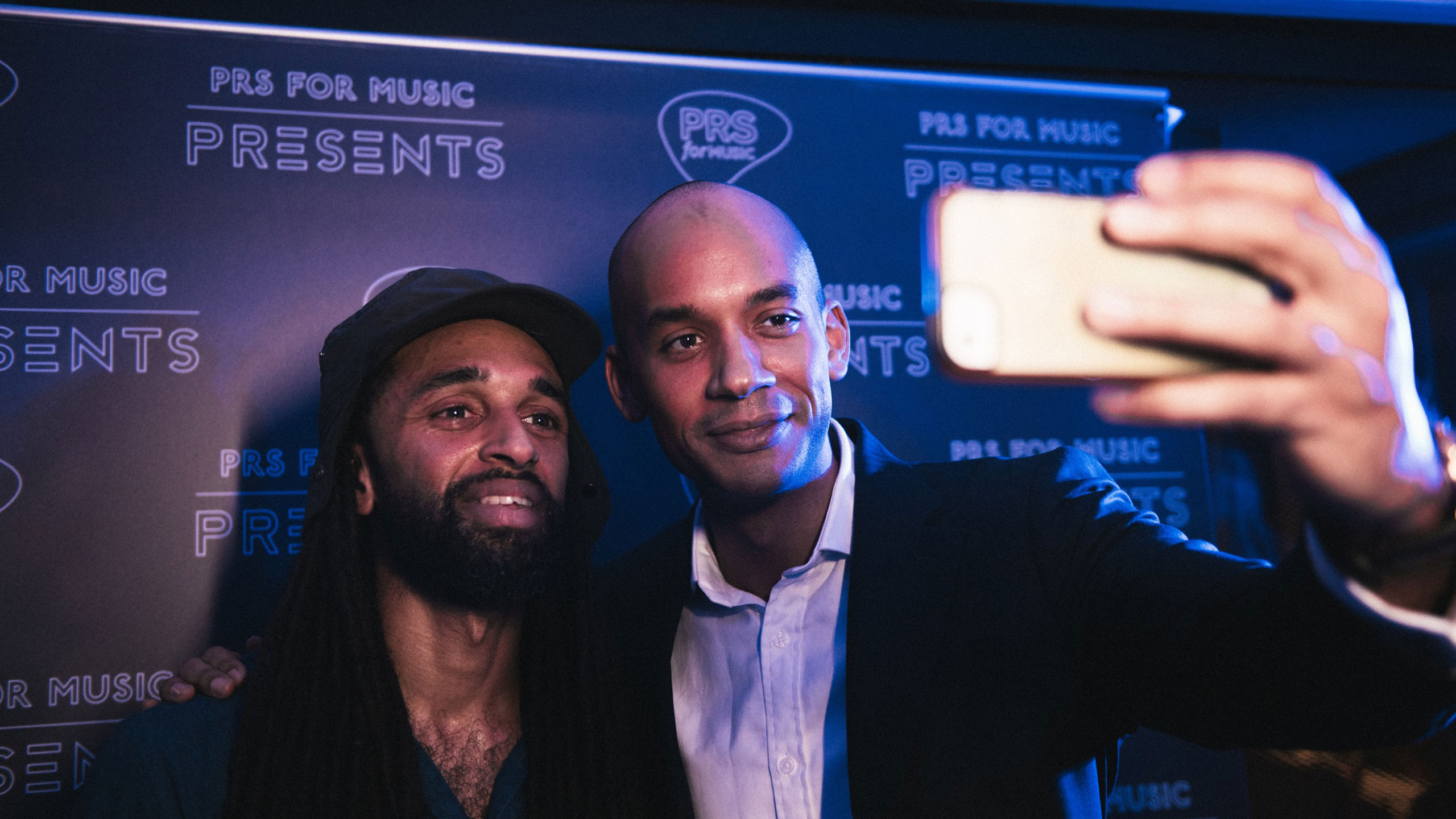 Chuka Umunna (PRS for Music ambassador) takes a selfie with Andrew Ashong in front of the PRS for Music Presents backdrop