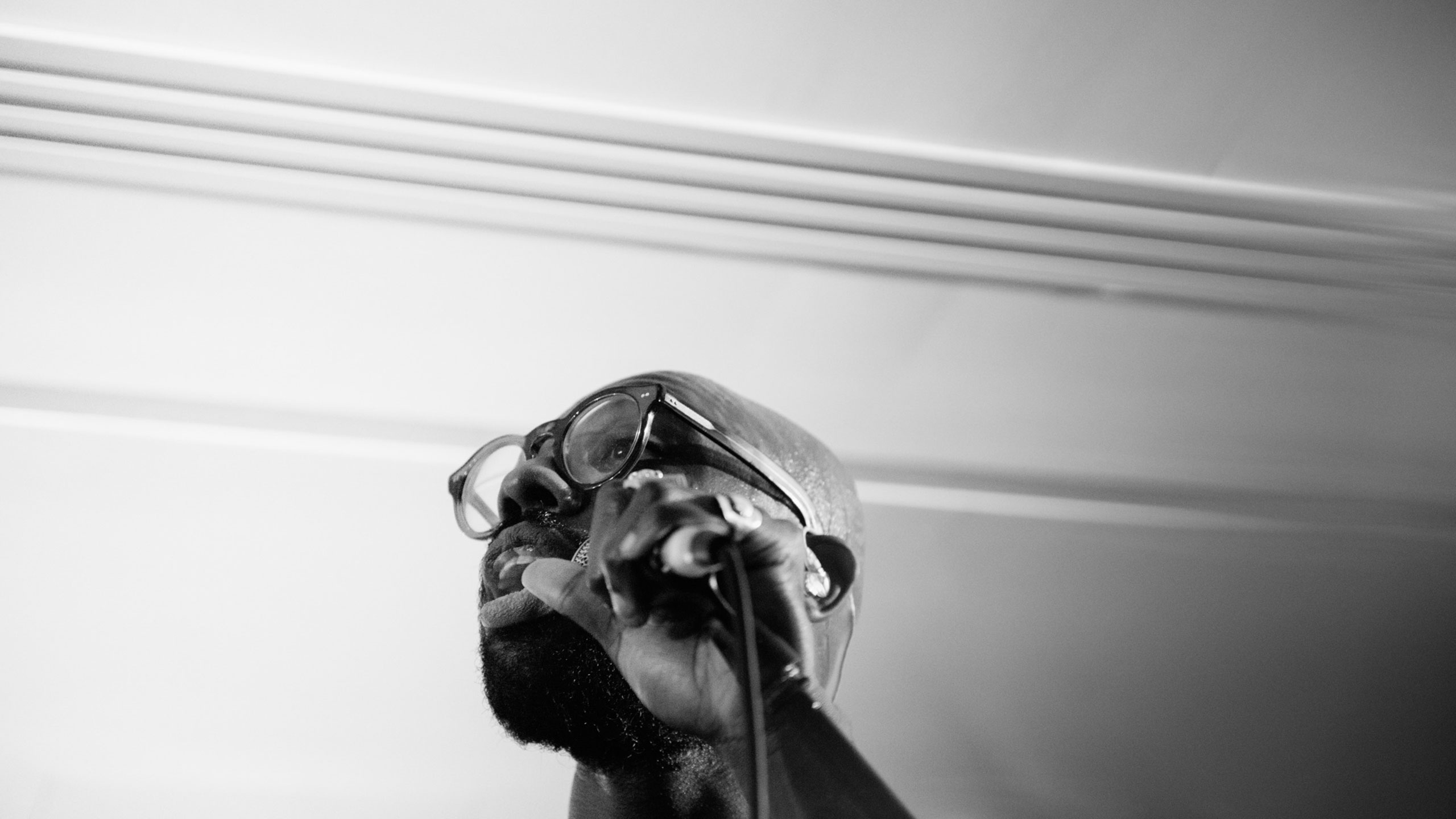 A close-up black and white photo of Ghost Poet singing live at PRS for Music Presents