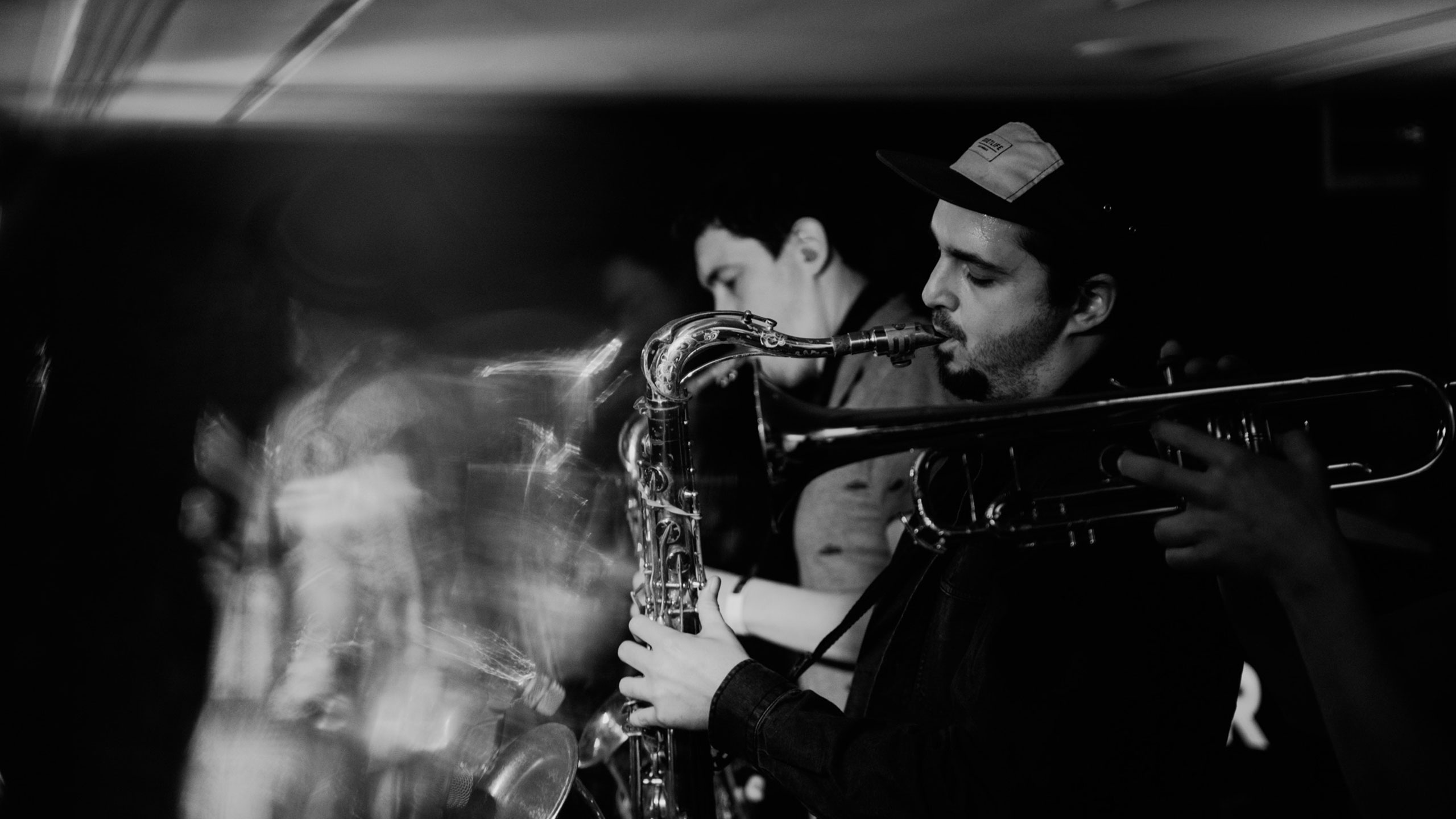 A black and white photo of two saxophonists from Dr Meaker performing live at PRS for Music Presents, with a blurred effect