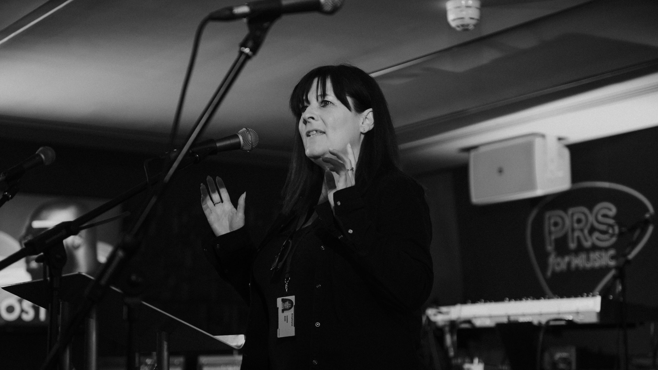 A black and white photo of Karen Buse, former executive director of membership and international, talking on stage at PRS for Music Presents