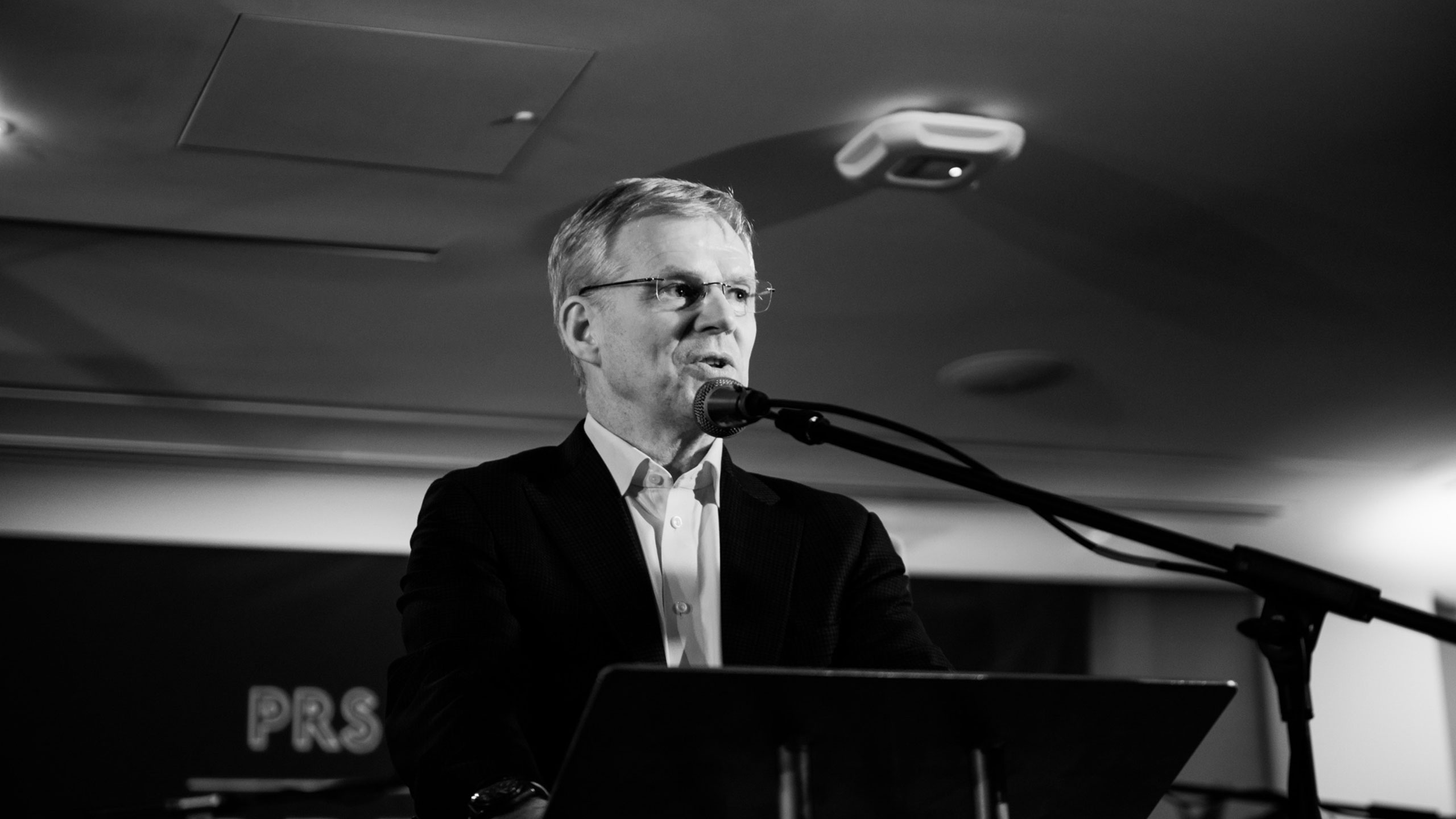 A black and white photo of Robert Ashcroft, chief executive of PRS for Music, talking on stage at PRS for Music Presents