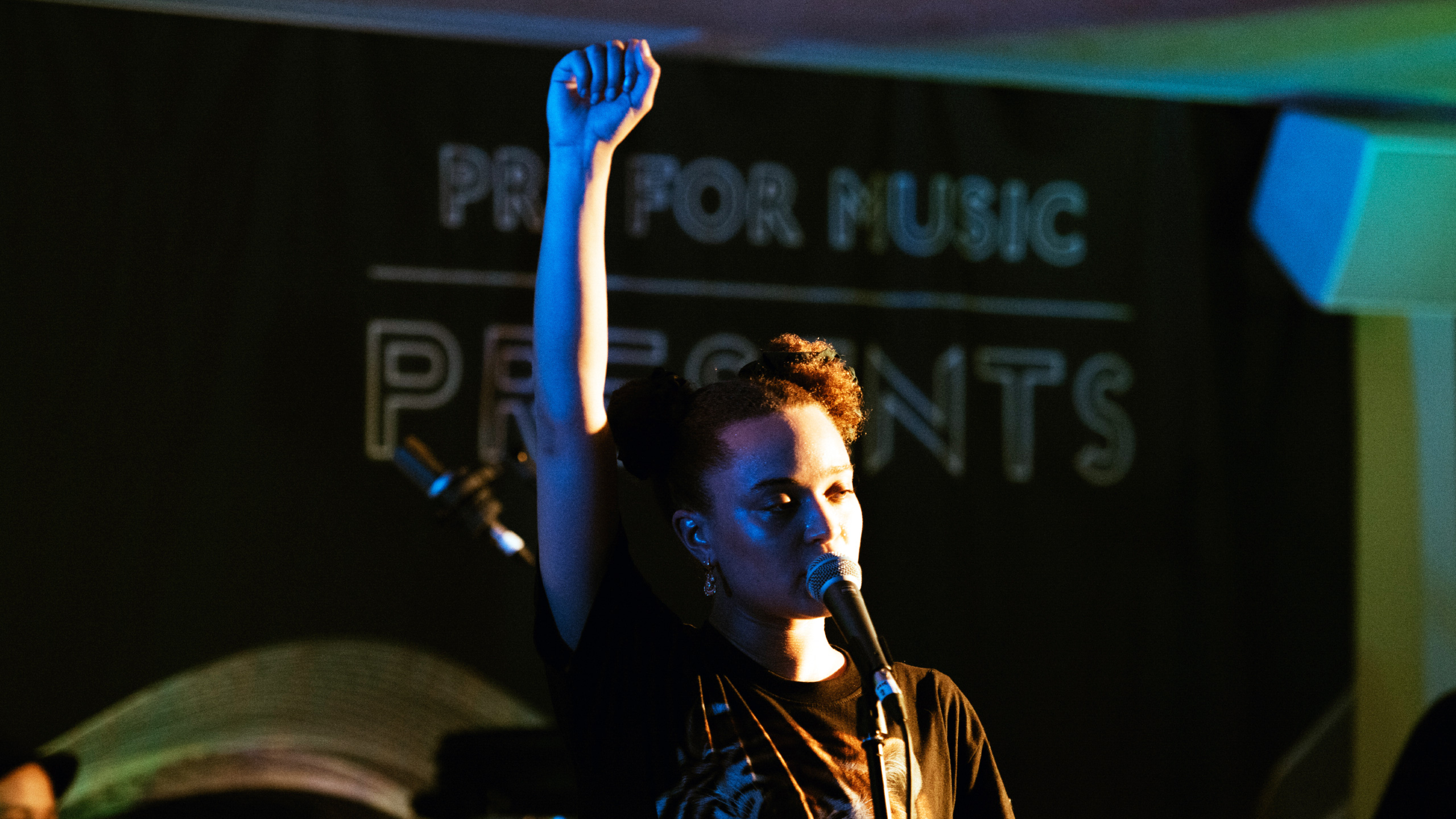 Connie Constance raises a clenched fist as she performs at PRS for Music Presents
