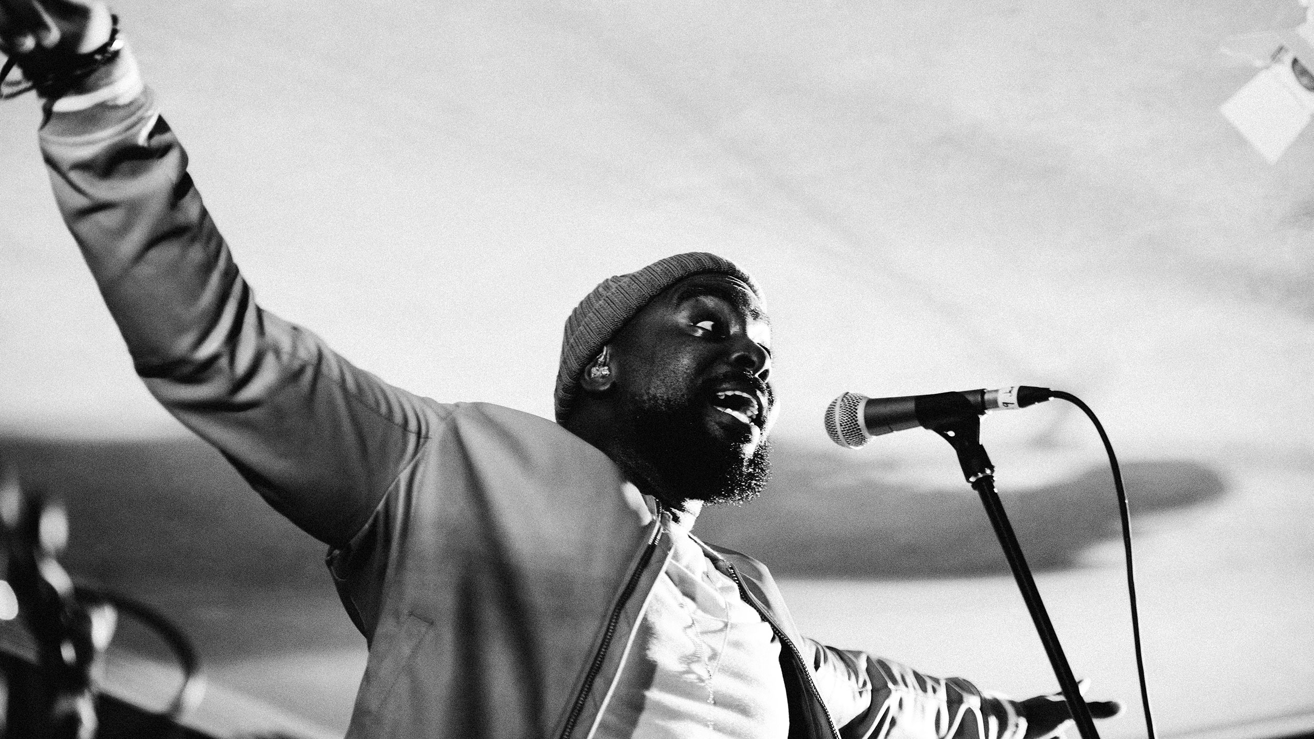 A black and white image of Jodie Abacus singing with his arms outstretched at PRS for Music Presents
