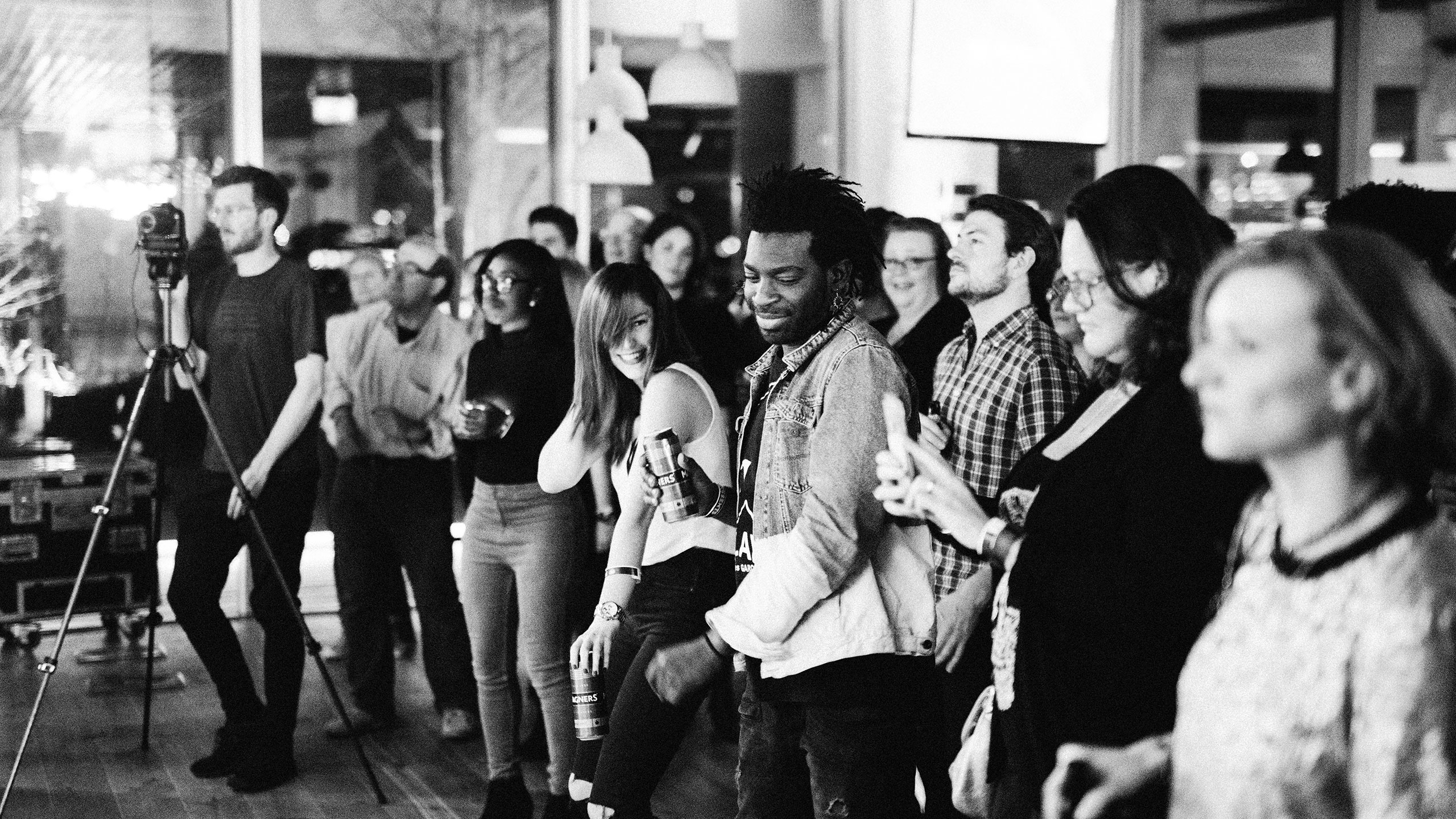 A black and white photo of the audience at PRS for Music Presents, including two people dancing and one taking a photo with their phone