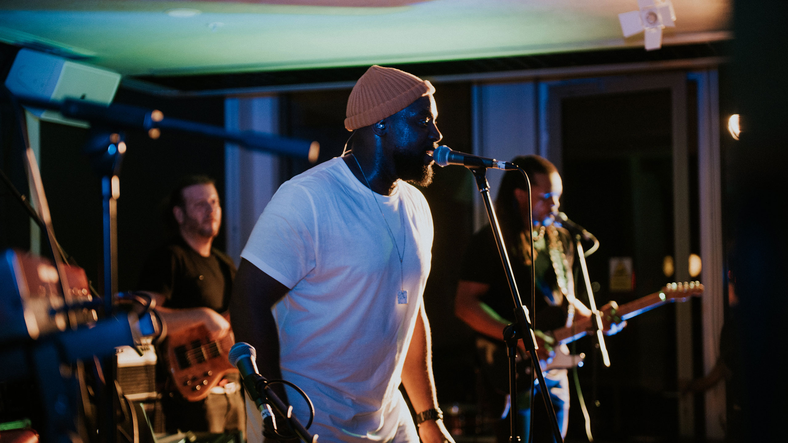 Jodie Abacus, wearing a white t shirt and orange beanie hat, sings into the microphone at PRS for Music Presents with a guitarist and bass guitarist visible behind him