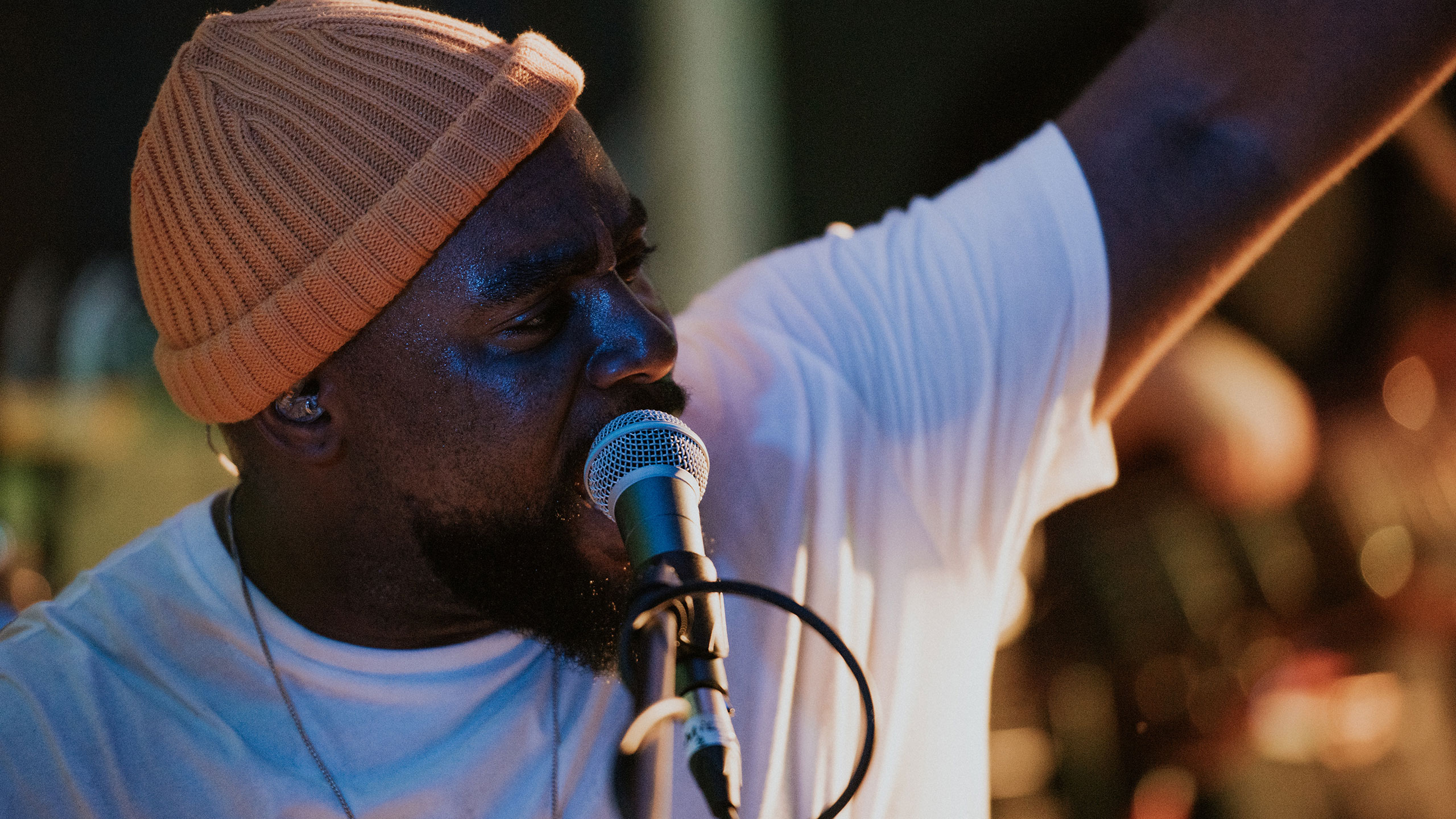 A close up photo of Jodie Abacus, wearing an orange beanie and white t shirt, singing into the microphone and raising his left arm at PRS for Music Presents