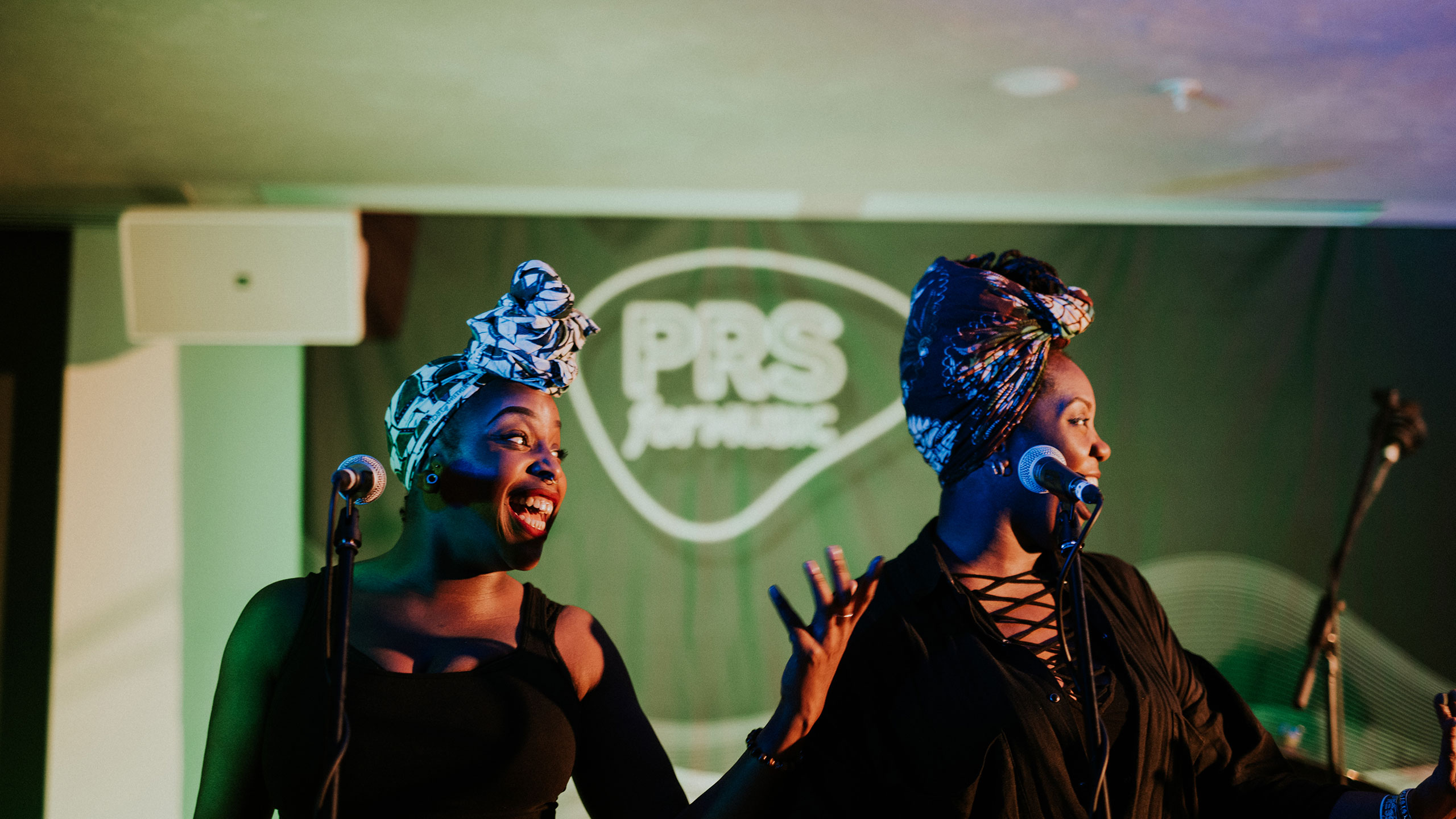 Two singers wearing colourful head wraps and black tops sing and smile to their left on stage at PRS for Music Presents