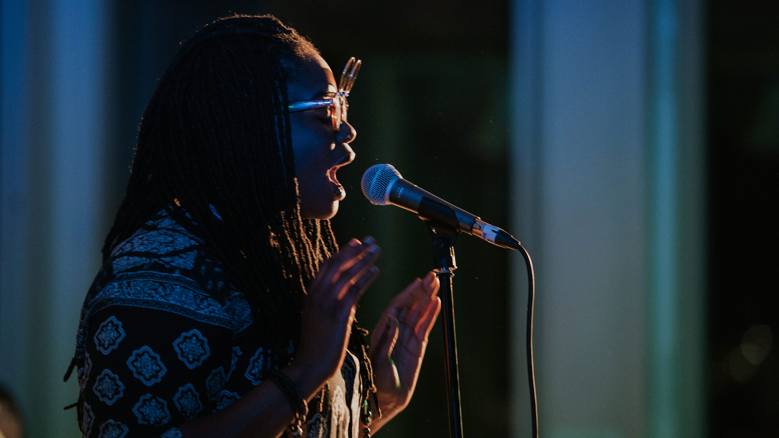 Speech Debelle wearing a patterned shirt and glasses sings and raises her hands to shoulder height at PRS for Music Presents