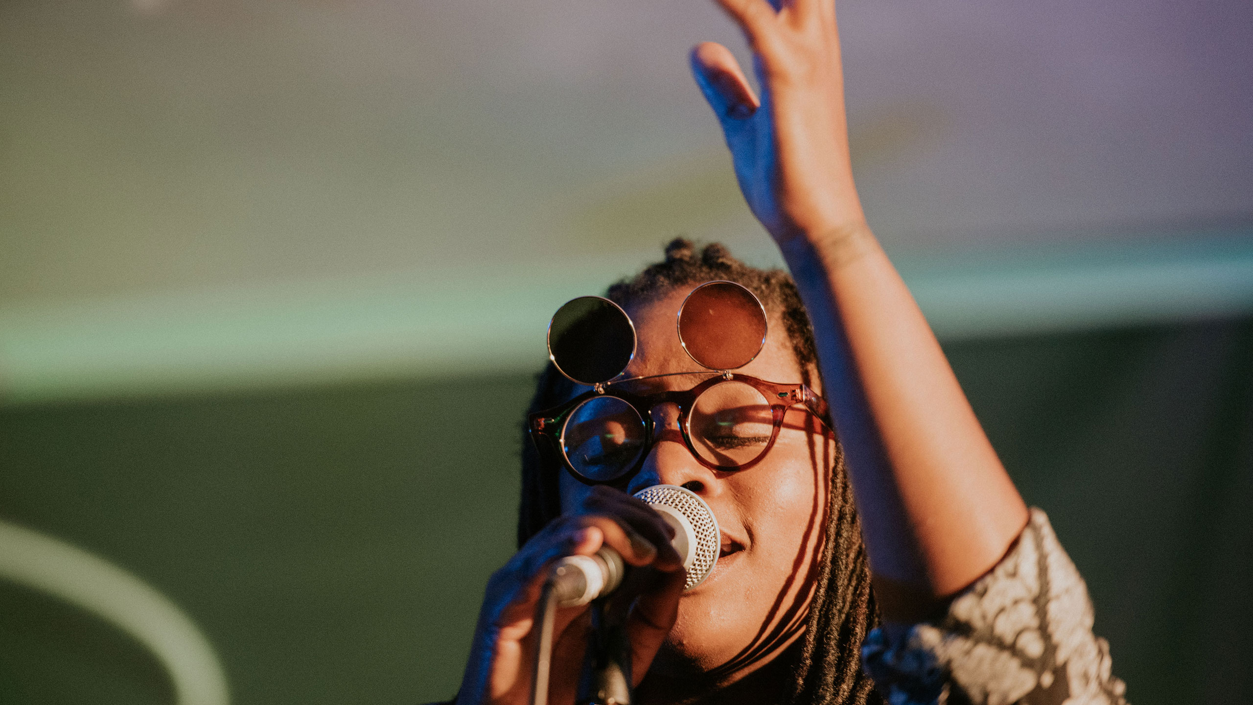 Speech Debelle sings into the microphone in her right hand and raises her left hand at PRS for Music Presents