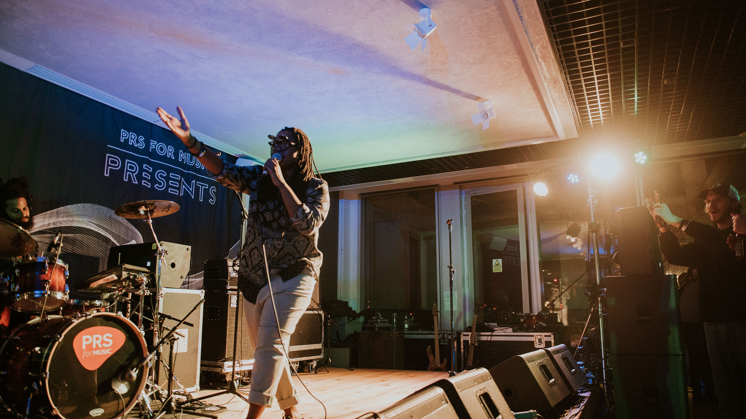 Speech Debelle walks across the stage with her arm outstretched at PRS for Music Presents