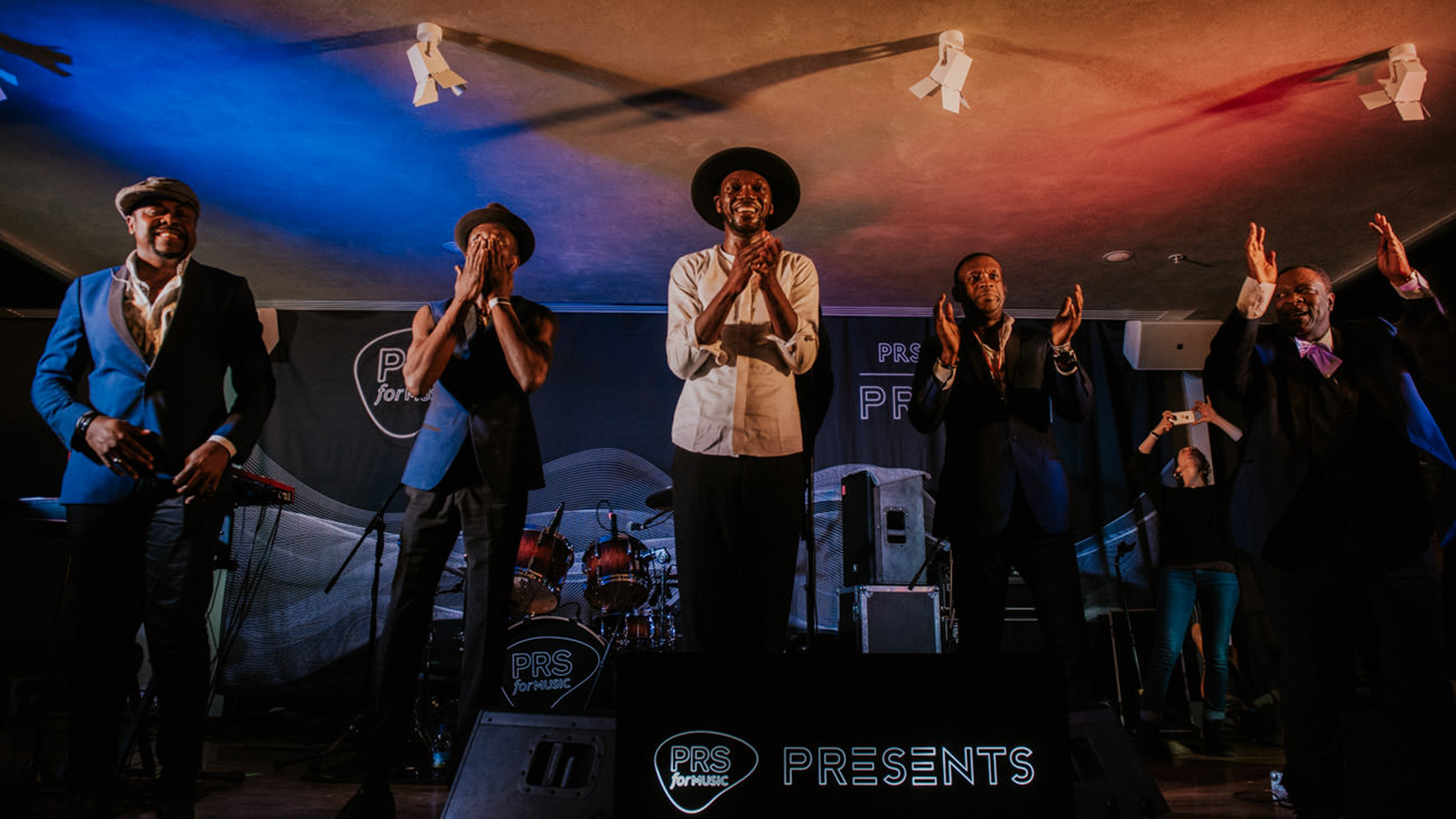 Baloji and his band clapping at the end of their set at PRS for Music Presents