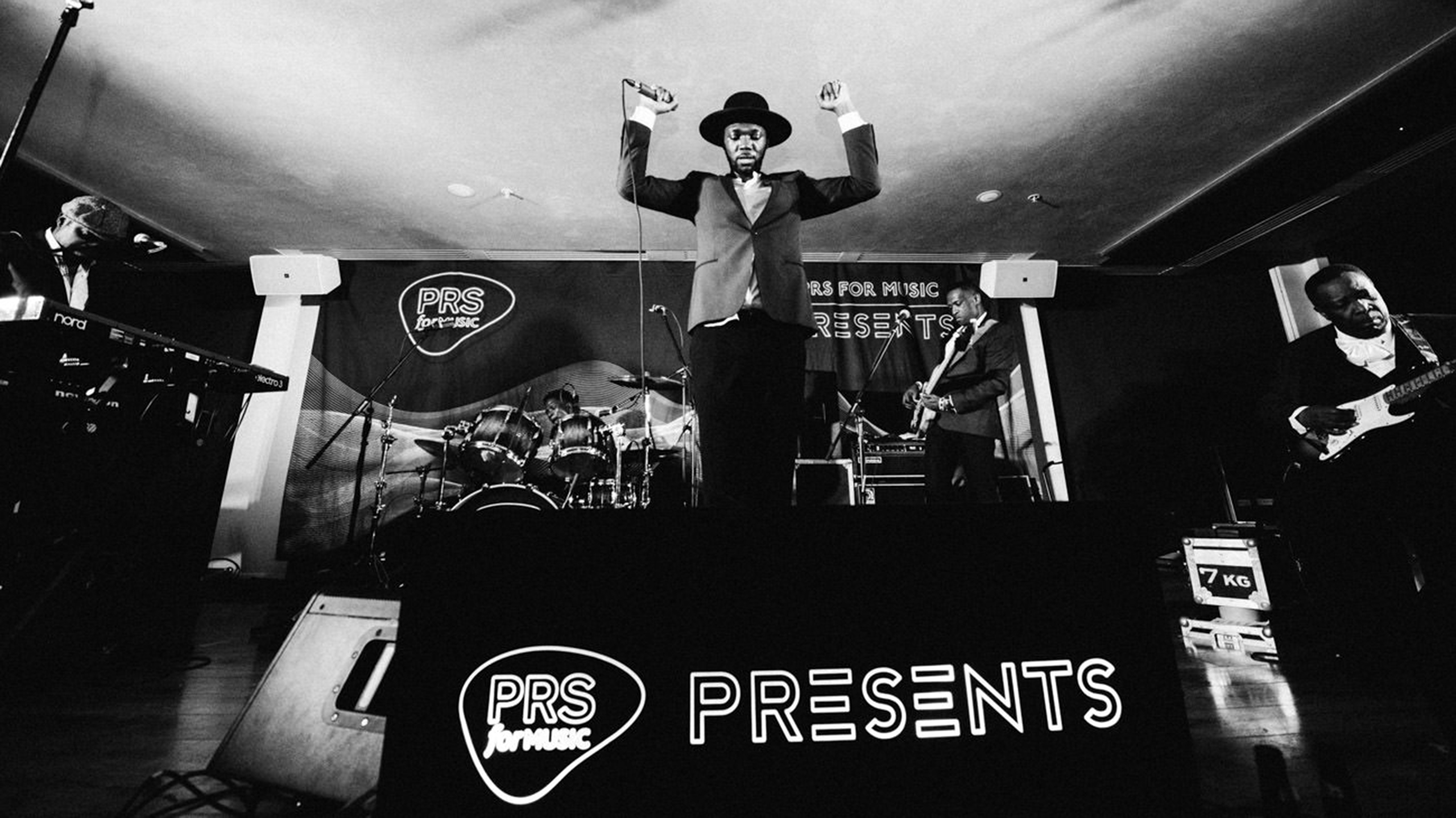 Baloji, wearing a black hat and jacket, raises his arms on stage at PRS for Music Presents, surrounded by his live band