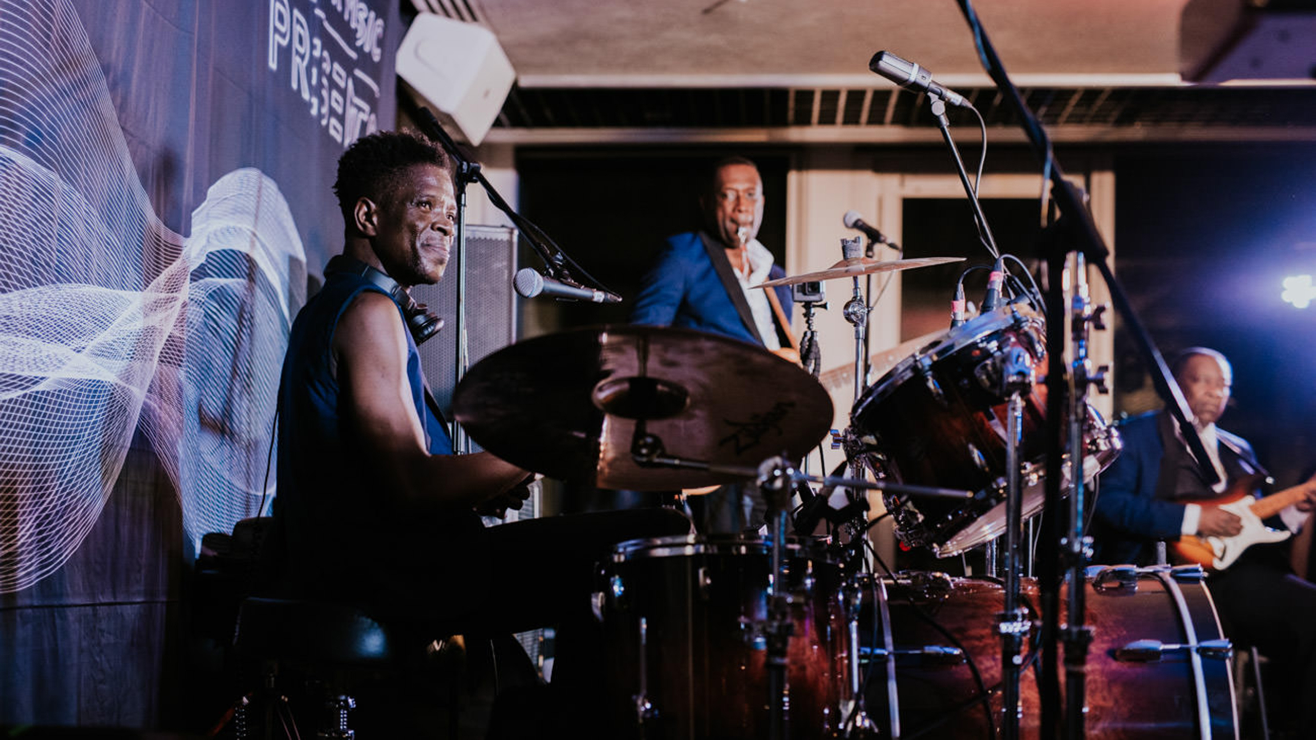 Baloji's drummer smiles on stage at PRS for Music Presents