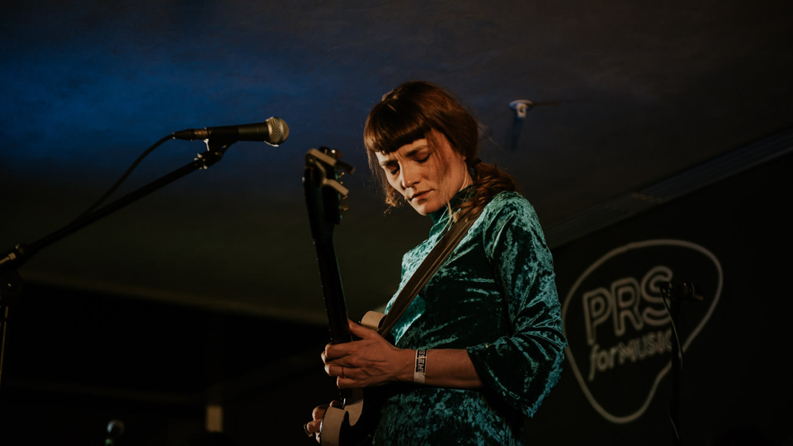 Halo Maud, wearing a green velvet dress, playing guitar on stage at PRS for Music Presents