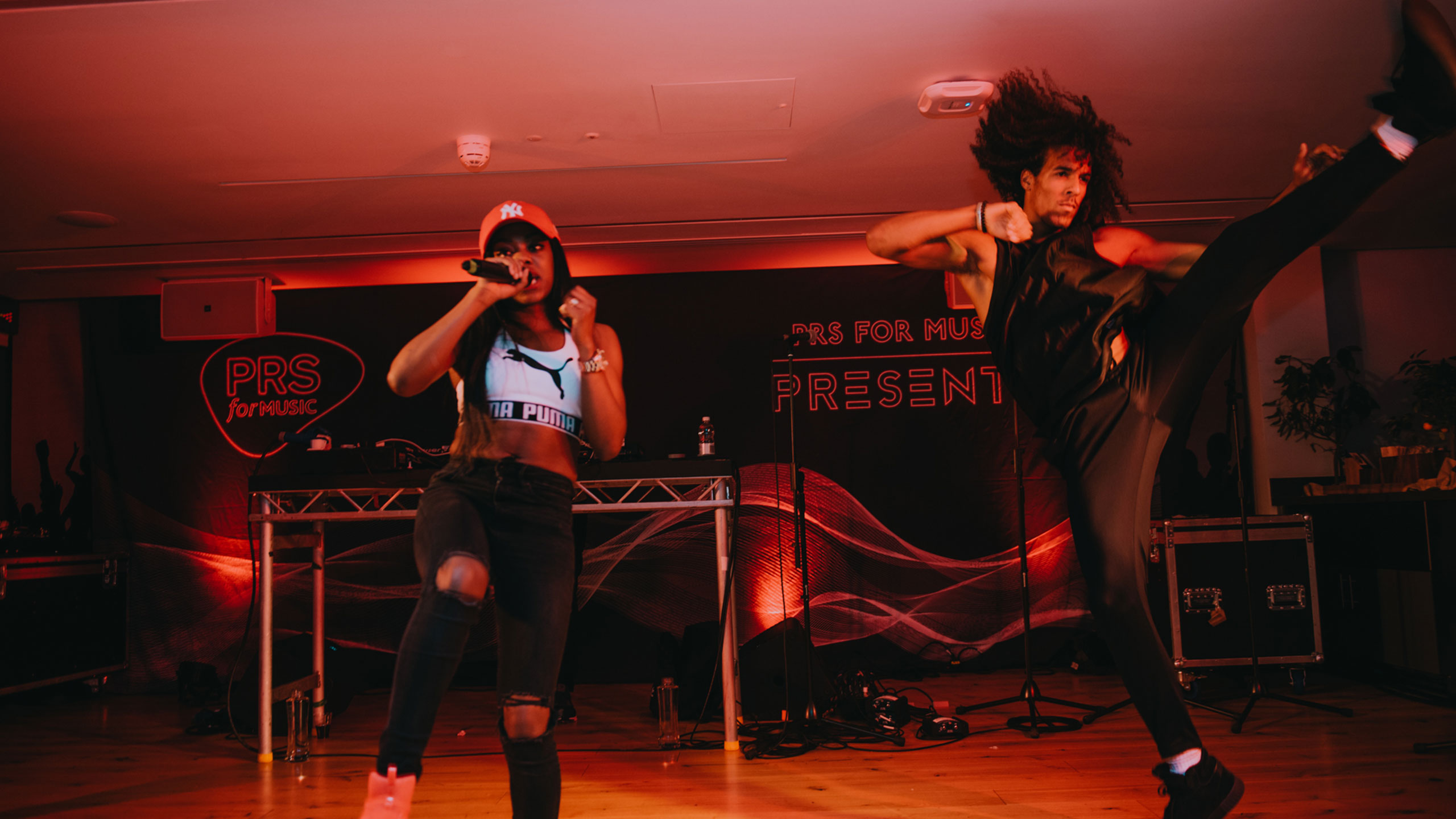 Lady Leshurr and a dancer doing a high kick performing at PRS for Music Presents